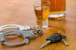 Image of a drink, car keys and handcuffs, indicating if you drink and drive you will get arrested.