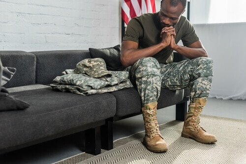 Military man sitting on couch think about his domestic violence charges.